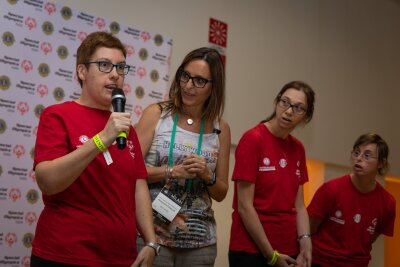 A woman wearing glasses a red t-shirt stands on a stage holding a microphone facing forward with three women standing in a row beside her and watching her speak.