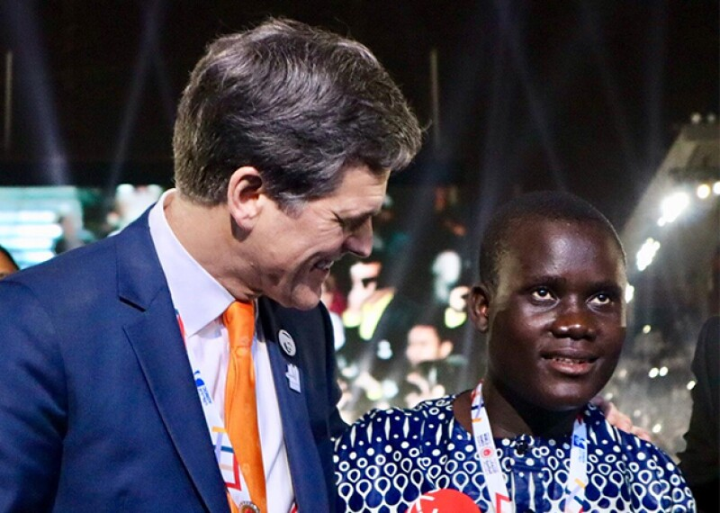 Timothy Shriver with Malachie on stage during the opening ceremony walking onstage with other athletes.