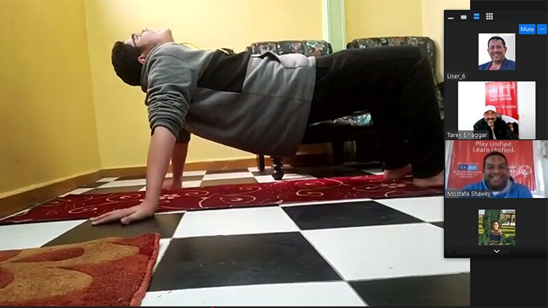 A screenshot from a Zoom video call, with the large frame featuring a boy lifting his body off the floor, facing up. The other participants smile from their Zoom windows.