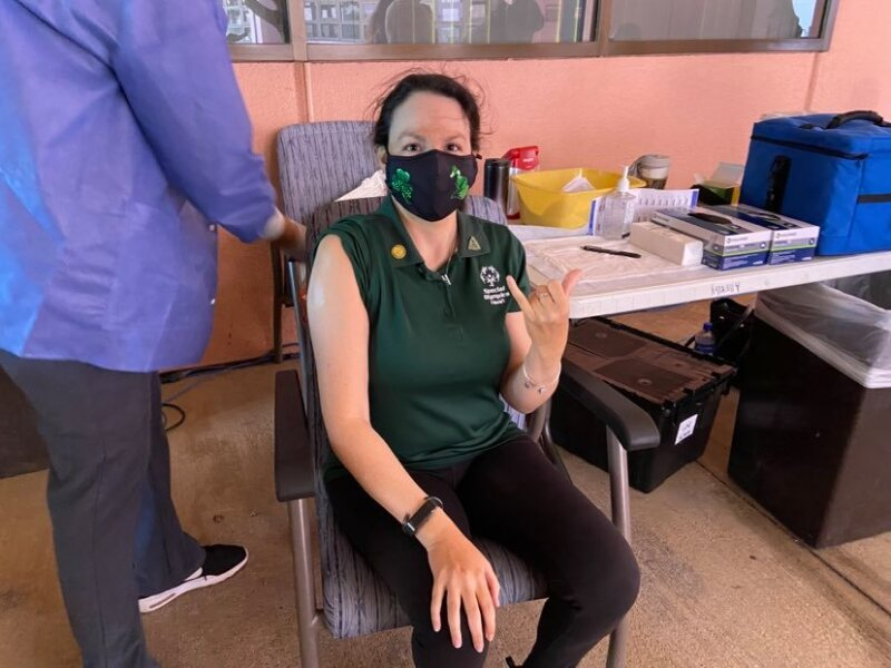 Renee Manfredi sits in a chair at a clinic with her sleeve rolled up to her shoulder right before she gets the vaccine.