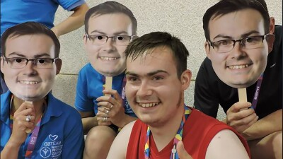 Niall sitting with three other athletes that are wearing masks of him.