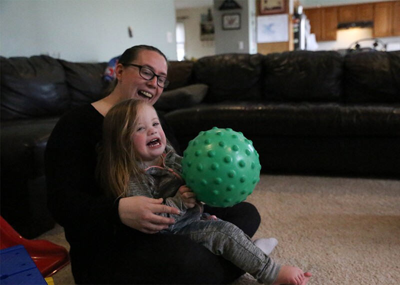 Child holding a ball and sitting on a woman's lap in a living room.