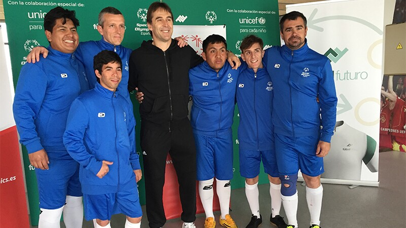 A group of young men in blue football kits surround an older man in a black tracksuit as they all stand with their arms around each other smiling at the camera.