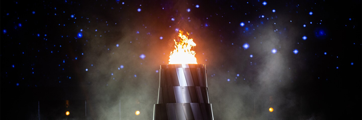 Eternal flame in front of a star filled sky.