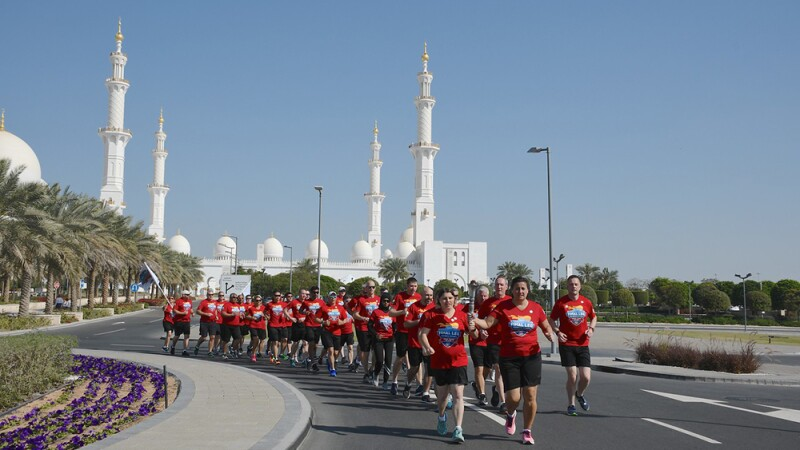 Sherri leads the Final Leg runners on the road with the Sheikh Zayed Grand Mosque in the background.