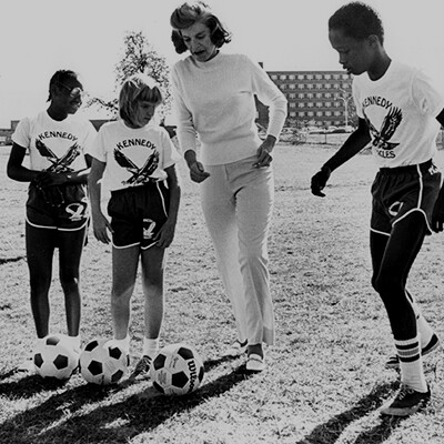Eunice Kennedy Shriver with three young athletes playing soccer.