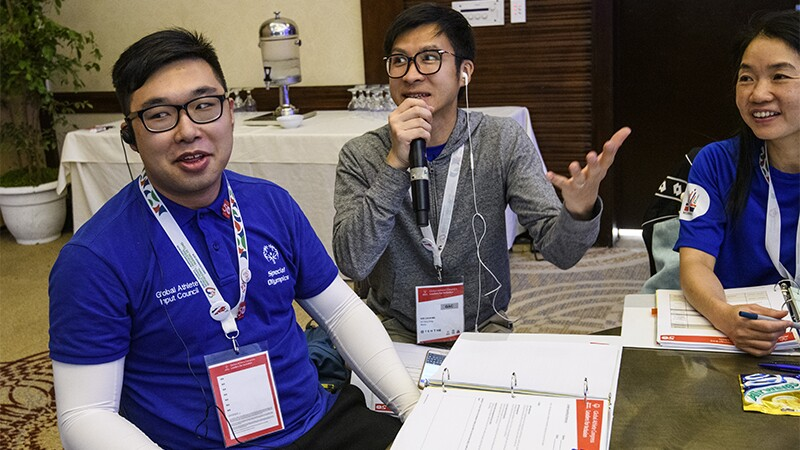 Attendees from SO Hong Kong participating in an activity during the Global Athletes Congress workshop; two males and one female are pictured; the male in the center of the group is speaking.