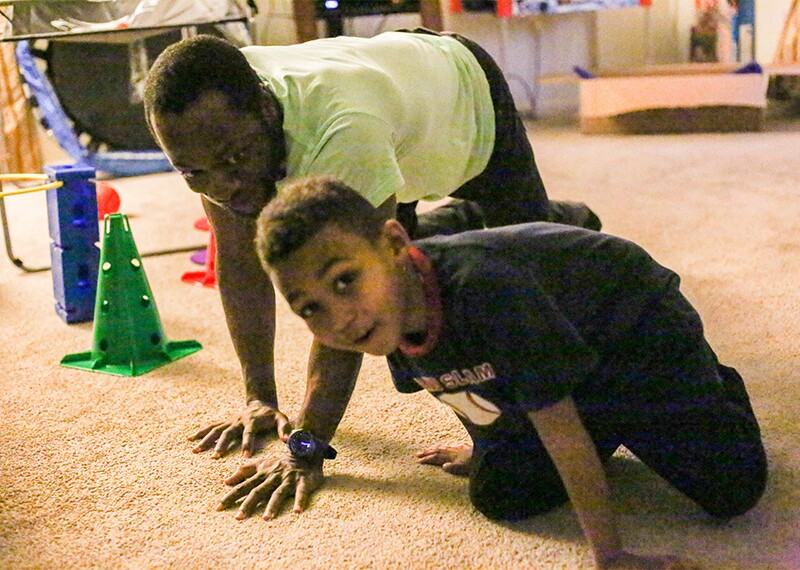 Young boy and man on the floor in a living room.