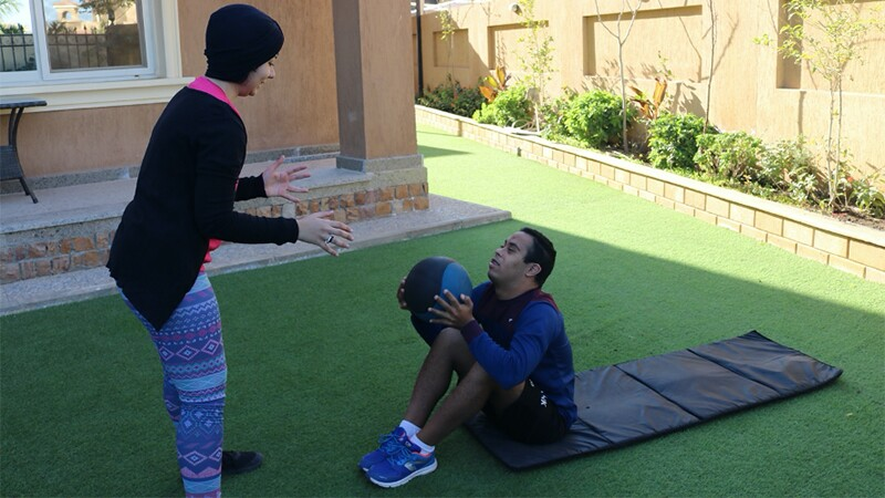 Two Youth Leaders face each other, one sitting on the ground in sit-up position and one standing up. The youth on the ground is handing a medicine ball to his partner as a part of a workout.