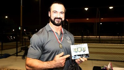 WWE Superstar, Drew McIntyre, holding Special Olympics welcome plaque.