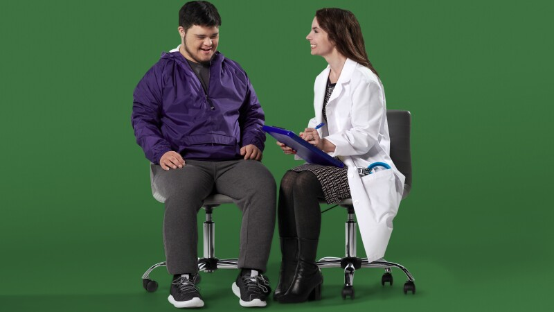 A Special Olympics Athlete sits with a Health Professional
