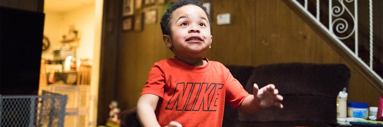 Young Boy walking through a living room.
