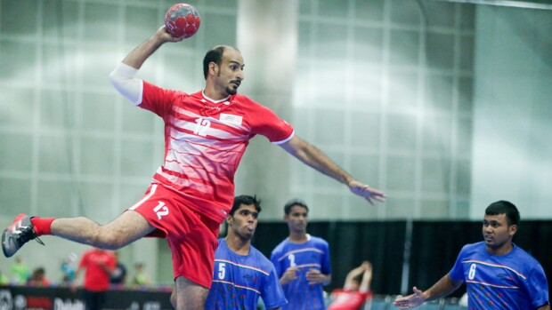 Handball athlete making a jump-shot while the opposing team watches.