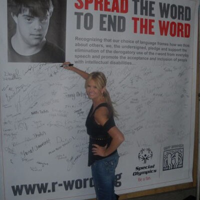 American television host, Nancy O'Dell, signs an r-word banner and pledges to end the word.