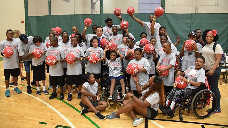 Sam Perkins along with a group of athletes hold red Play Unified balls in a gymnasium posing for a group photo.