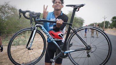 Abhishek Gogoi holding his bike with one hand and giving the peace sign with the other.