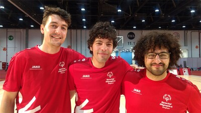 """Three brothers from Belgium """"Smash Brother"""" standing side by side with their arms around one another all wearing red Special Olympics Belgium t-shirts."""