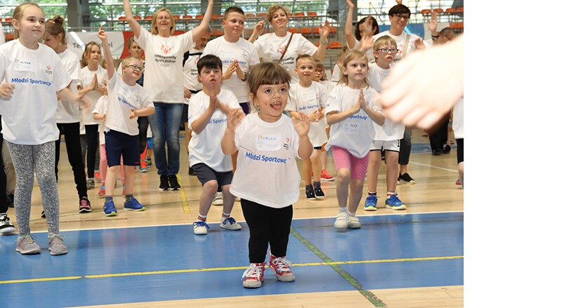 Young and Unified athletes and volunteers in a gymnasium warming up. A young female athlete is in the foreground.