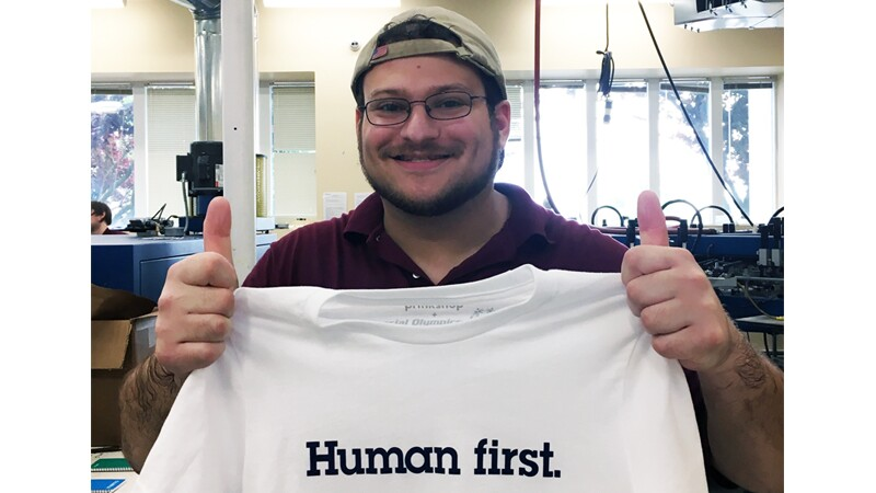 Josh, Spectrum employee, standing in a storage area giving a double thumbs up and holding a shirt that reads, Human first.