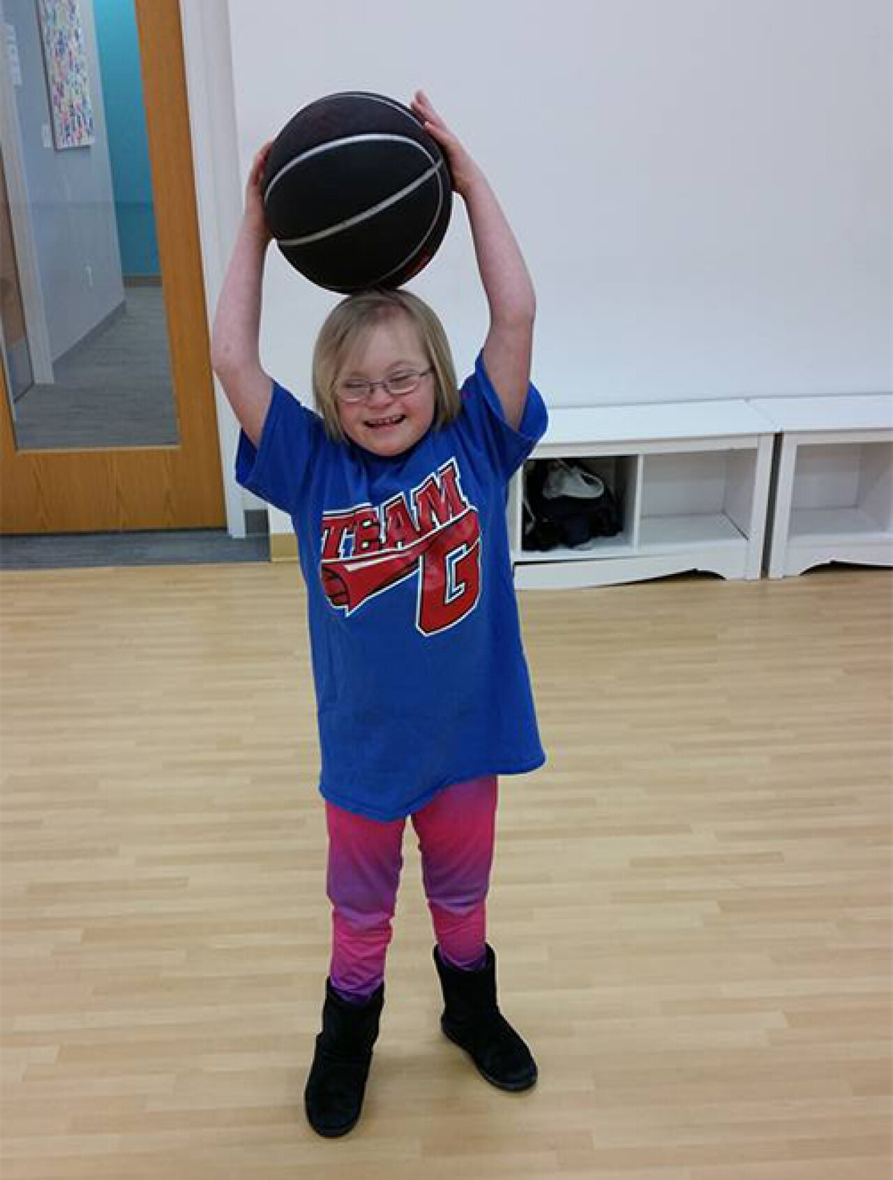 Violet holds a basketball on her head