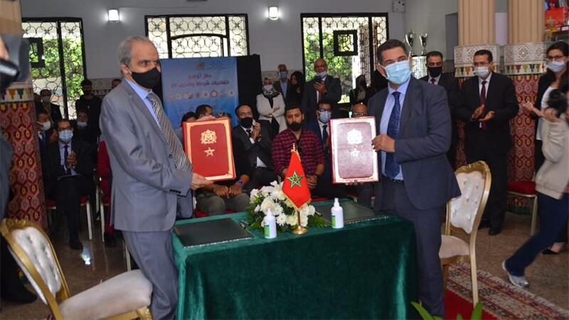 Two masked men dressed in suits hold envelopes containing the MoU, with the Moroccan flag at their table. Behind them, the room is full of a small, masked crowd.