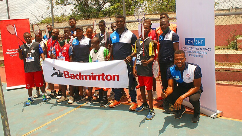 A group of athletes, coaches, and Unified partners pose together in a group holding a banner with the word AirBadminton on it, with a Special Olympics banner on their right and a Stavros Niarchos Foundation banner on their left.