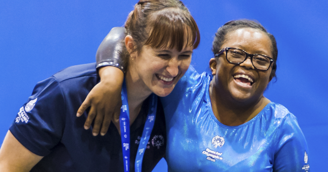 A smiling Special Olympics gymnast wraps her arm around her coach as they celebrate her performance at the 2018 Special Olympics USA Games