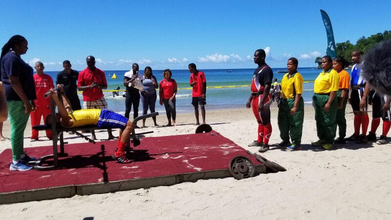 Powerlifting competitors wait for their turns to lift weights. They are lined up in front of a platform on the beach. one Olympian is on the bench lifting a weight.