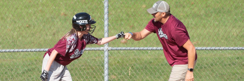 Female baseball player fist-bumping a coach.