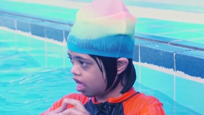 Young athlete in the pool with a colorful swim cap and swim suite on.