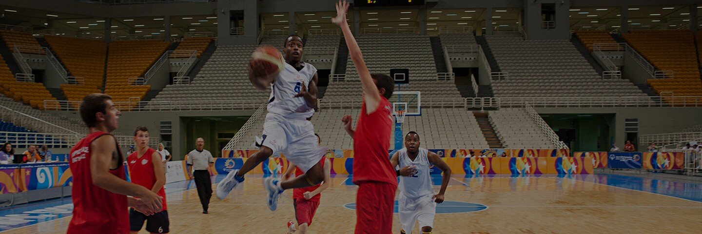 Athletes playing basketball on a court.