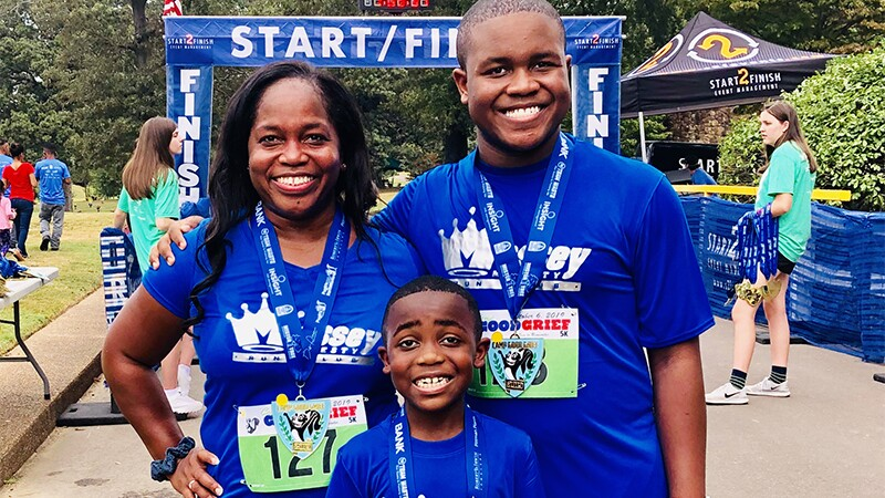 Eric, his mom, and his brother smile after finishing a race.