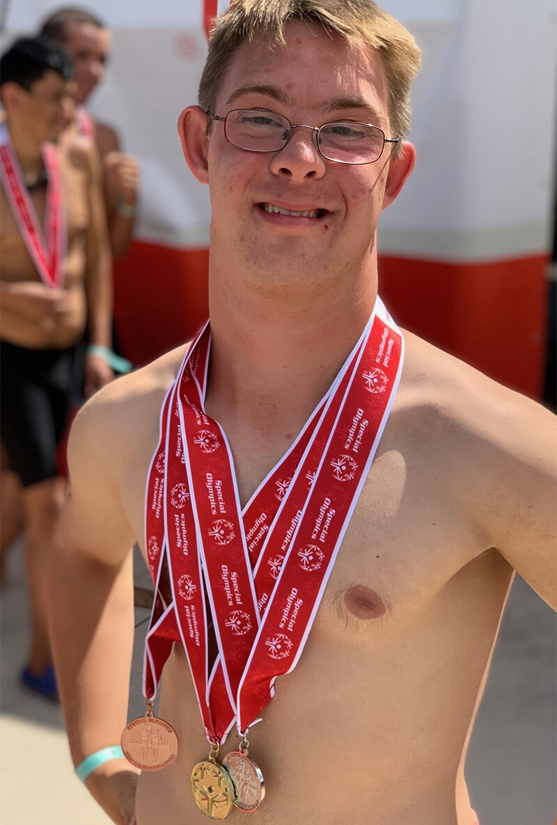 Chris Nikic proudly poses wearing three medals he won in swimming at a Special Olympics Florida competition.