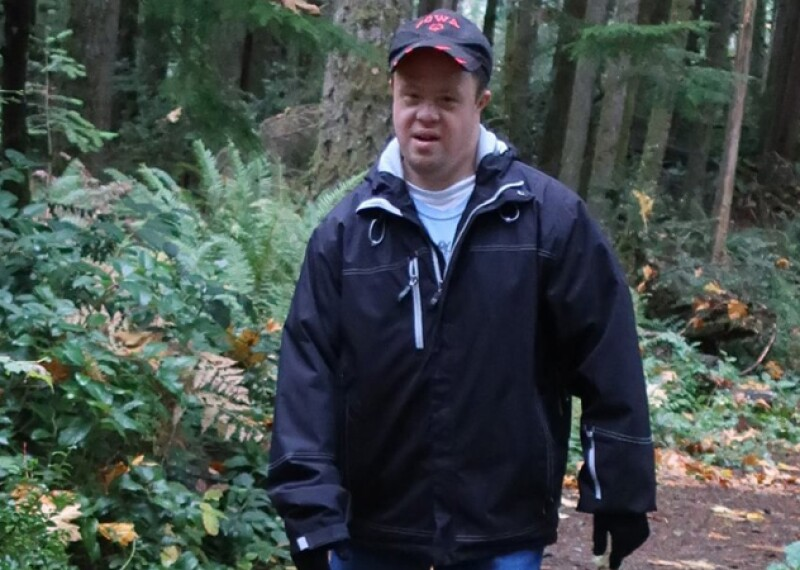 Special Olympics Washington athlete Reid Zimmer walking on a path through the woods.