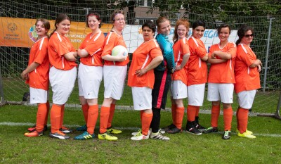 Eleven women wearing orange and white football kits stand in front of a football/soccer net on a football pitch.
