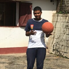 Sammy standing outside with a basketball in hand.