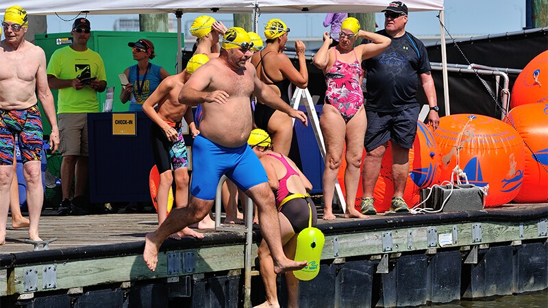 One athlete plunging into the water, another climbing up the ladder; other athletes and spectators are watching from behind on the docks.