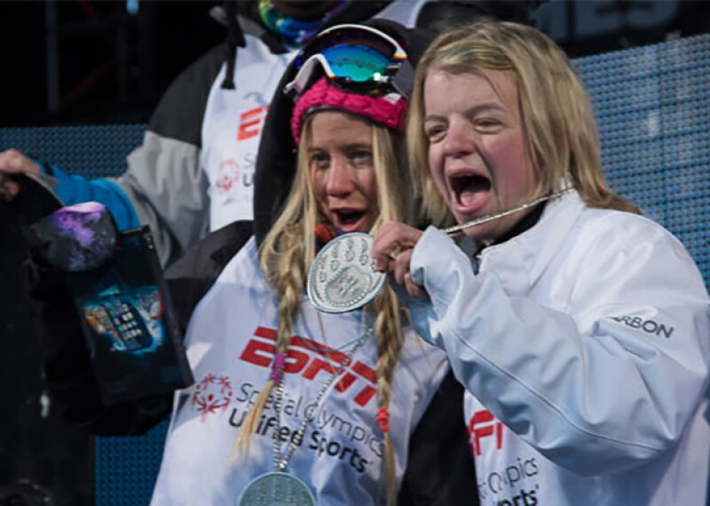 Special Olympics athlete Daina Hannah at X-Games with Hanna Teter showing off medals.