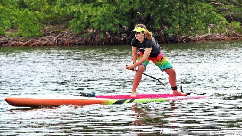 Special Olympics athlete stand up paddleboards down waterway.