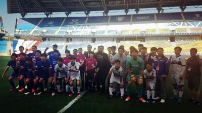 The Unified football match in collaboration with Incheon United FC and Suwon Samsung Bluewings took place on July 18th in Korea. A group of unified players stand in a row on the field with the bleacher behind them.