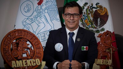 A man, smiling in a suit with official patches on it, sits at a desk in front of a Mexican flag and next to an AMEXCO plaque.
