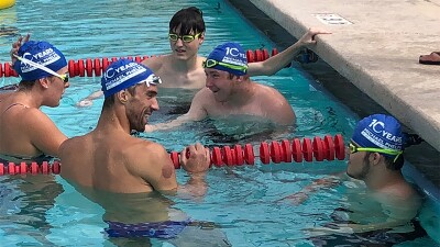 Michael Phelps in the pool with four other athletes holding onto the ropes and talking