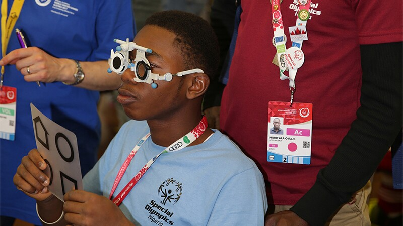 Athlete from Nigeria receiving an eye exam as observers look on.