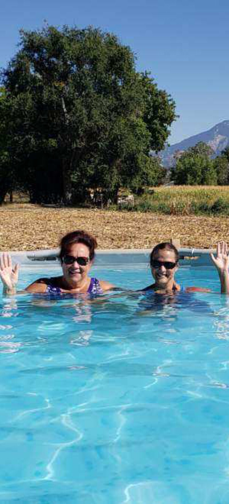 Amber and her mom in their outdoor pool with the mountains in the background.