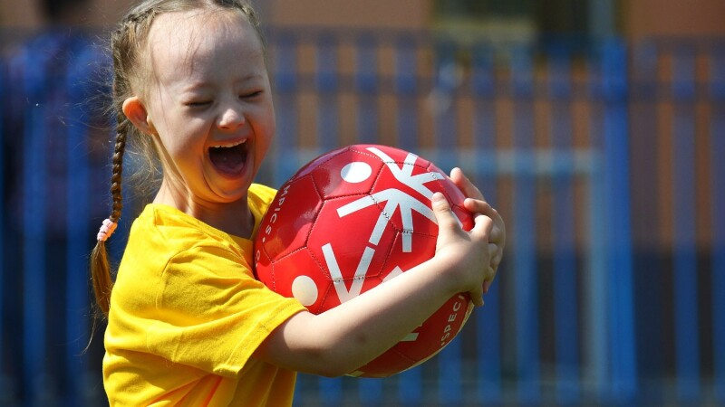 A young girls in a yellow t-shirt holds a red football. Her eyes are closed and she is shouting in glee.