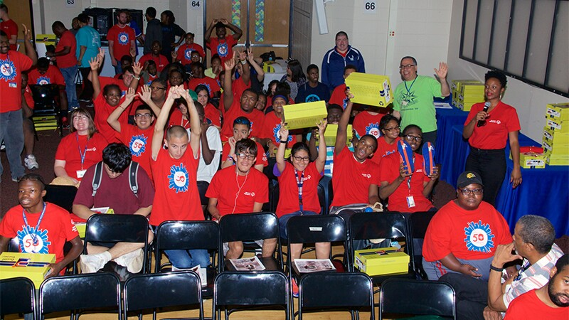 Students at the Southside Occupational Academy High School celebrate receiving athletic shoes during the Shoe Giveaway.