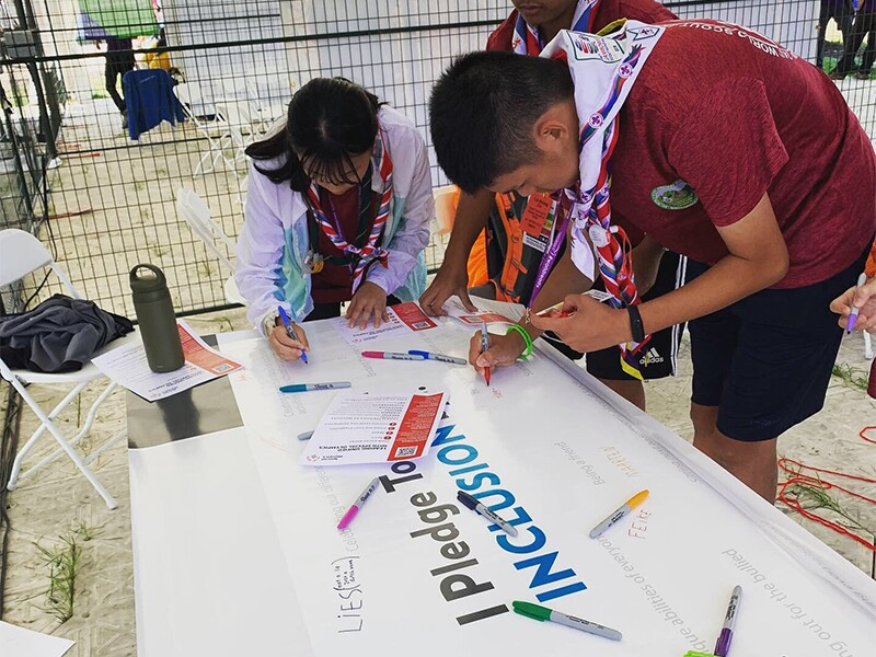 A group of three scouts are standing at a table signing the Inclusion Pledge.