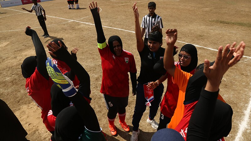 Female players stand in circle with hands in air.