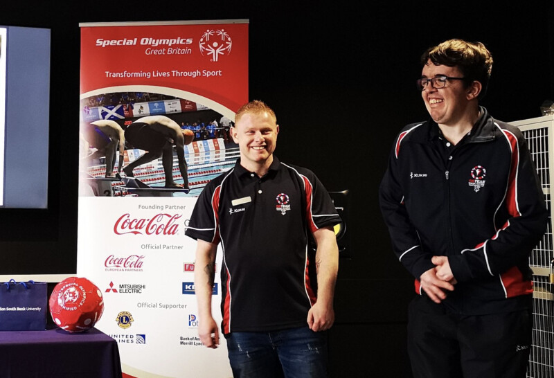 Two Special Olympics Great Britain athletes smiling on a stage standing beside a red Special Olympics Unified ball and a Special Olympics branded pull-up banner.png