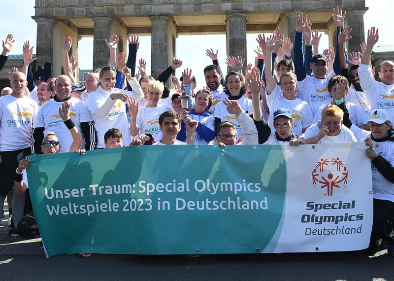 German delegation celebrating in a group with their hands up in the air.